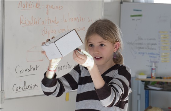 Une écolière essaye de découvrir le contenu d'une boîte mystère (Photo: Yves René Kayonga)